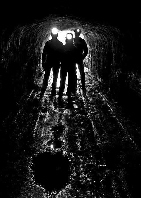 picture of a tunnel with 3 miners at the opening with head lamps on