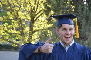 photo of a man graduating with a thumbs up